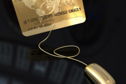 A gold credit card connected to a golden computer mouse on a black background