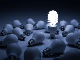 Lit energy saving lightbulb amongst unlit incandescent bulbs