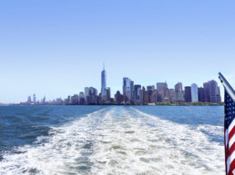 Lower Manhattan view from cruise ship or yacht with the flag of the United States of America in New York. Scenic view to NY Downtown and city centre. Staten Island Ferry. Tourists cruising in boat.